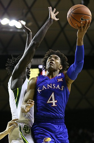 Kansas guard Devonte' Graham (4) is fouled by Baylor Bears forward Jo Lual-Acuil Jr. (0) on his way to the bucket during the first half, Saturday, Feb. 11, 2018 at Ferrell Center in Waco, Texas.