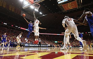Kansas guard Lagerald Vick (2) swoops in for a bucket against Iowa State forward Cameron Lard (2) during the second half, Tuesday, Feb. 13, 2018 at Hilton Coliseum in Ames, Iowa.