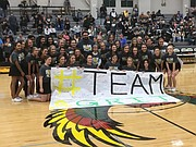 Free State's spirit squad poses for a picture with Nolan Henderson, middle, and his daughter Ella Avant during halftime of the FSHS boys basketball game on Tuesday, Feb. 13, 2018 at FSHS. The spirit squad read messages of support during a ceremony for Henderson's 4-month-old son Grit, who is is battling a rare skeletal muscle cancer.