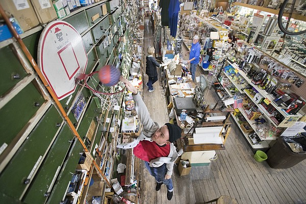 Ernst and Son Hardware employee Eddie Wilson passes time shooting on a basketball hoop affixed to the tall system of drawers at the shop as Lynda Allen, daughter of the late Rod Ernst, talks with her husband, Gary Allen, on Thursday, Feb. 15, 2018 at the downtown store, 826 Massachusetts St.