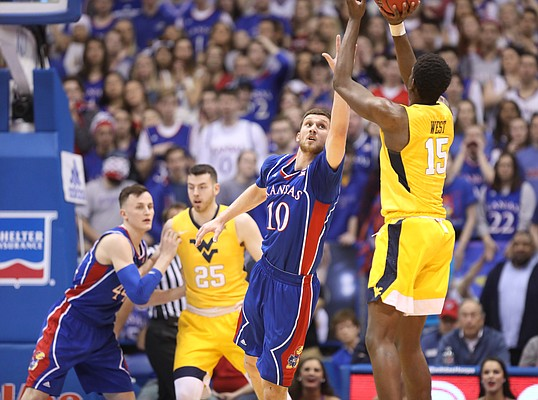 Kansas guard Sviatoslav Mykhailiuk (10) defends against a three from West Virginia forward Lamont West (15) during the first half, Saturday, Feb. 17, 2018 at Allen Fieldhouse.