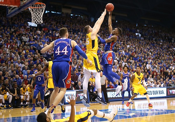 Kansas guard Lagerald Vick (2) hangs for a shot over West Virginia forward Maciej Bender (25) during the first half, Saturday, Feb. 17, 2018 at Allen Fieldhouse.