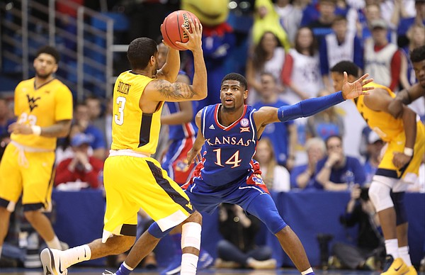 Kansas guard Malik Newman (14) defends against a pass from West Virginia guard James Bolden (3) during the second half, Saturday, Feb. 17, 2018 at Allen Fieldhouse.
