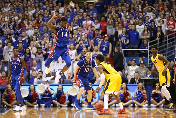 Kansas guard Malik Newman (14) elevates to defend against a shot from West Virginia guard Daxter Miles Jr. (4) during the second half, Saturday, Feb. 17, 2018 at Allen Fieldhouse.