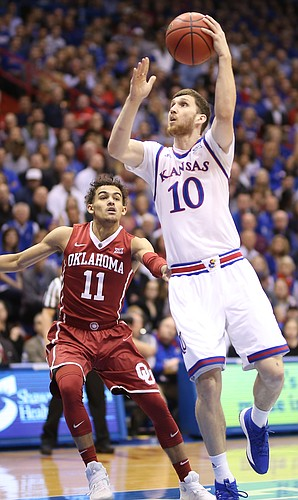 Kansas guard Sviatoslav Mykhailiuk (10) turns to the bucket past Oklahoma guard Trae Young (11) during the first half, Monday, Feb. 19, 2018 at Allen Fieldhouse.