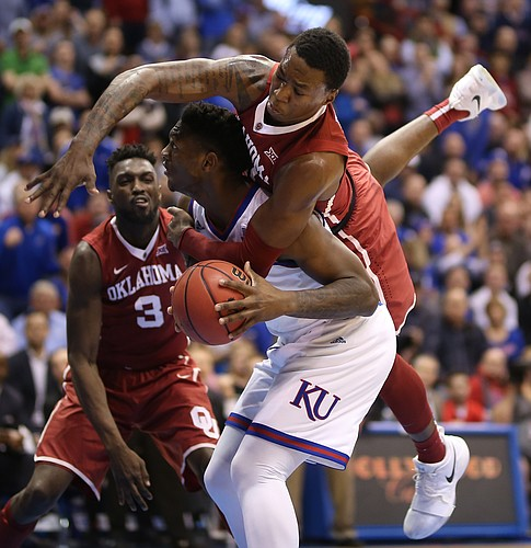 Oklahoma forward Kristian Doolittle (21) falls on top of Kansas forward Silvio De Sousa (22) in the post during the first half, Monday, Feb. 19, 2018 at Allen Fieldhouse.