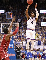 Kansas guard Devonte' Graham (4) pulls up for a three in front of Oklahoma guard Rashard Odomes (1) during the second half, Monday, Feb. 19, 2018 at Allen Fieldhouse.