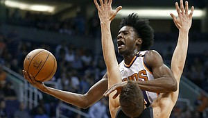 Phoenix Suns forward Josh Jackson drives as Dallas Mavericks forward Maximilian Kleber (42)) defends, while Suns forward TJ Warren (12) watches during the first half of an NBA basketball game Wednesday, Jan. 31, 2018, in Phoenix. (AP Photo/Ross D. Franklin)