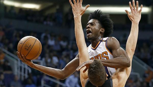 Phoenix Suns forward Josh Jackson drives as Dallas Mavericks forward Maximilian Kleber (42)) defends, while Suns forward TJ Warren (12) watches during the first half of an NBA basketball game Wednesday, Jan. 31, 2018, in Phoenix. (AP Photo/Ross D. Franklin)