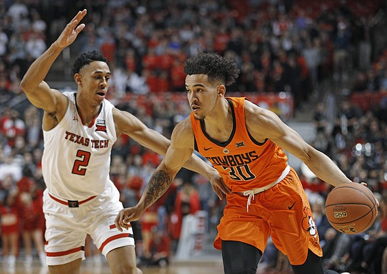 Oklahoma State's Jeffrey Carroll (30) drives the ball around Texas Tech's Zhaire Smith (2) during the first half of an NCAA college basketball game Tuesday, Jan. 23, 2018, in Lubbock, Texas. (AP Photo/Brad Tollefson)