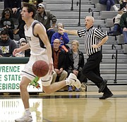 High school basketball official Phil Lombardi trails the play while keeping a 10-second count during Saturday's game between Free State and Bishop Miege at FSHS.