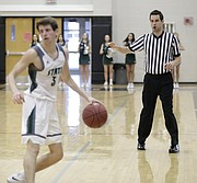 High school basketball official Mark Samsel does a 5-second count while watching the ball in Saturday's game between Free State and Bishop Miege at FSHS.