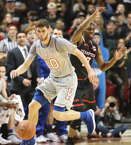 Kansas guard Sviatoslav Mykhailiuk (10) strips a pass from Texas Tech guard Keenan Evans (12) during the first half on Saturday, Feb. 24, 2018 at United Supermarkets Arena.