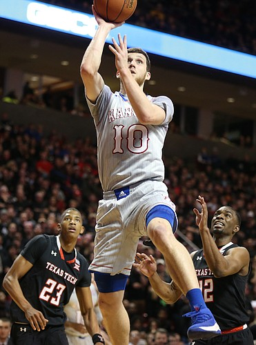 Kansas guard Sviatoslav Mykhailiuk (10) puts back a shot before Texas Tech guard Keenan Evans (12) and Texas Tech guard Jarrett Culver (23) during the first half on Saturday, Feb. 24, 2018 at United Supermarkets Arena.