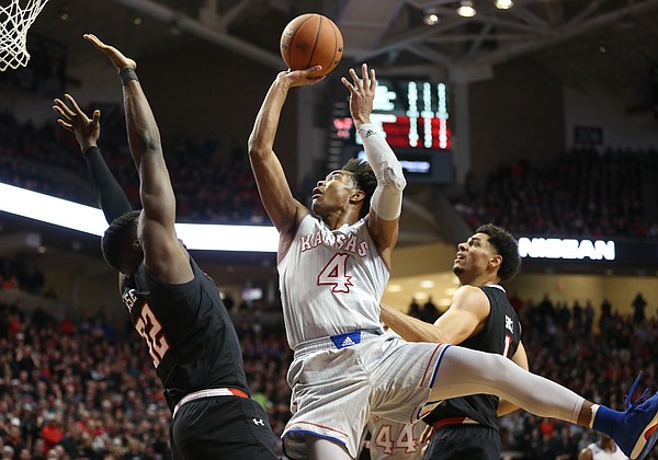 Kansas guard Devonte' Graham (4) puts up a shot after a foul from Texas Tech center Norense Odiase (32) during the second half on Saturday, Feb. 24, 2018 at United Supermarkets Arena.
