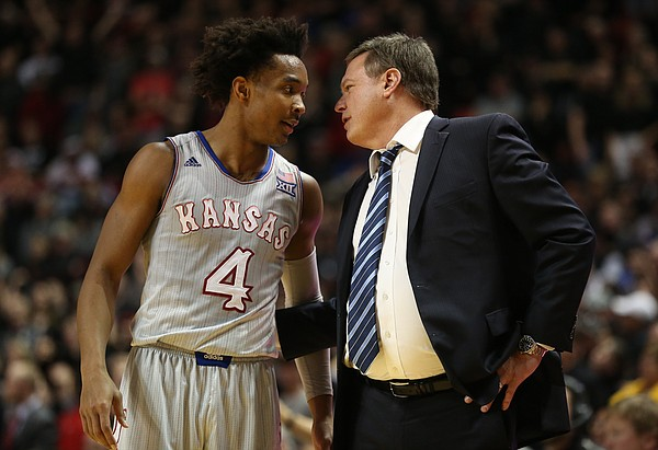 Kansas guard Devonte' Graham (4) talks with Kansas head coach Bill Self during a break in the second half on Saturday, Feb. 24, 2018 at United Supermarkets Arena.
