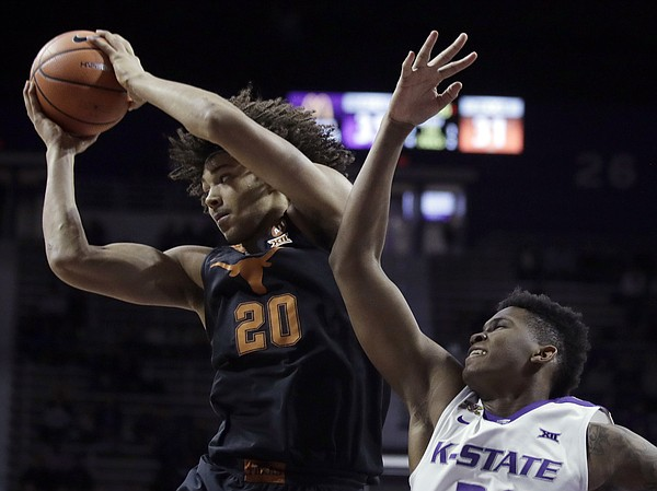 Texas forward Jericho Sims (20) pulls down a rebound against Kansas State forward James Love III, right, during the second half of an NCAA college basketball game in Manhattan, Kan., Wednesday, Feb. 21, 2018. Kansas State defeated Texas 58-48.