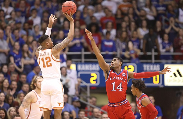Kansas guard Malik Newman (14) guards against a shot from Texas guard Kerwin Roach II (12) during the first half on Monday, Feb. 26, 2018 at Allen Fieldhouse.