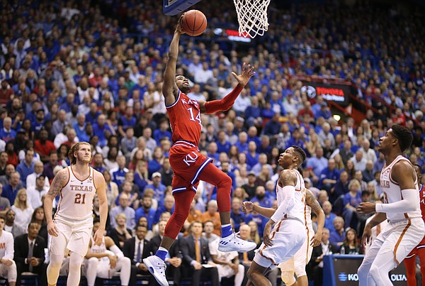 Kansas guard Malik Newman (14) elevates for a dunk against the Texas defense during the first half on Monday, Feb. 26, 2018 at Allen Fieldhouse.