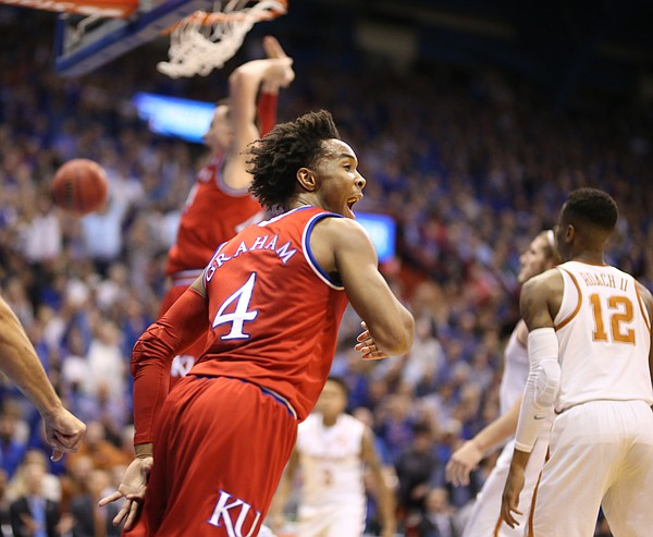 Kansas guard Devonte' Graham (4) celebrates a dunk from Kansas forward Mitch Lightfoot (44) during the first half on Monday, Feb. 26, 2018 at Allen Fieldhouse.