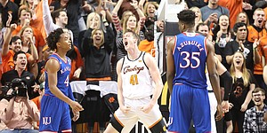 Oklahoma State forward Mitchell Solomon (41) explodes between Kansas guard Devonte' Graham (4) and Kansas center Udoka Azubuike (35) after a dunk and a Kansas foul during the first half, Saturday, March 3, 2018 at Gallagher-Iba Arena, in Stillwater, Okla.