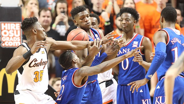 Kansas forward Silvio De Sousa (22) and Kansas guard Lagerald Vick (2) tangle with Oklahoma State forward Yankuba Sima (35) for a loose ball during the first half, Saturday, March 3, 2018 at Gallagher-Iba Arena, in Stillwater, Okla.
