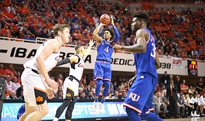 Kansas guard Devonte' Graham (4) pulls up for a three against Oklahoma State guard Kendall Smith (1) during the second half, Saturday, March 3, 2018 at Gallagher-Iba Arena, in Stillwater, Okla.