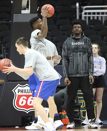 Kansas center Udoka Azubuike watches from the sidelines as teammates Kansas forward Mitch Lightfoot and Kansas forward Silvio De Sousa run through drills during a shoot around on Wednesday, March 7, 2018 at Sprint Center in Kansas City, Mo.