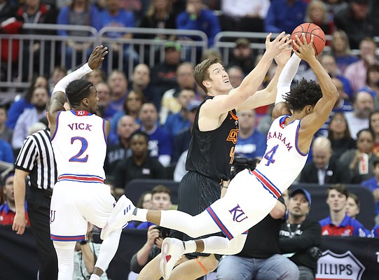 Kansas guard Devonte' Graham (4) yanks a rebound away from Oklahoma State forward Mitchell Solomon (41) during the first half, Thursday, March 8, 2018 at Sprint Center in Kansas City, Mo.