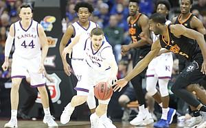 Kansas guard Sviatoslav Mykhailiuk (10) picks off a pass to Oklahoma State guard Tavarius Shine (5) during the first half, Thursday, March 8, 2018 at Sprint Center in Kansas City, Mo.