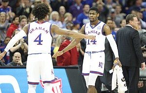 Kansas guard Devonte' Graham (4) and Kansas guard Malik Newman (14) slap hands during a KU run in the first half, Thursday, March 8, 2018 at Sprint Center in Kansas City, Mo.