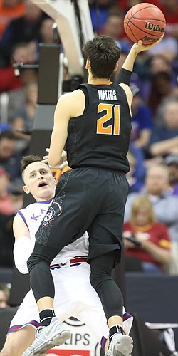 Kansas forward Mitch Lightfoot (44) takes a charge from Oklahoma State guard Lindy Waters III (21) during the second half, Thursday, March 8, 2018 at Sprint Center in Kansas City, Mo.