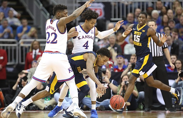 Kansas forward Silvio De Sousa (22) and Kansas guard Devonte' Graham (4) pressure West Virginia guard Daxter Miles Jr. (4) during the first half, Saturday, March 10, 2018 at Sprint Center in Kansas City, Mo.