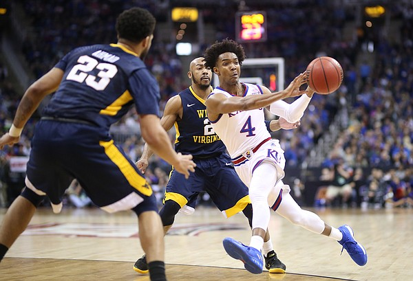 Kansas guard Devonte' Graham (4) pushes the ball to the wing past West Virginia guard Jevon Carter (2) and West Virginia forward Esa Ahmad (23) during the first half, Saturday, March 10, 2018 at Sprint Center in Kansas City, Mo.