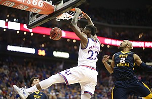 Kansas forward Silvio De Sousa (22) finishes a lob jam against West Virginia guard Jevon Carter (2) during the first half, Saturday, March 10, 2018 at Sprint Center in Kansas City, Mo.