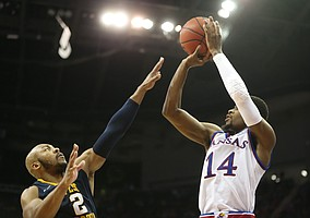 Kansas guard Malik Newman (14) puts up a three from the corner over West Virginia guard Jevon Carter (2) during the second half, Saturday, March 10, 2018 at Sprint Center in Kansas City, Mo.