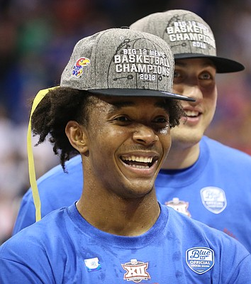 Kansas guard Devonte' Graham (4) smiles as he watches highlights from the Big 12 Tournament following the JayhawksÕ 81-70 win over the Mountaineers in the championship game of the Big 12 Tournament, Saturday, March 10, 2018 at Sprint Center in Kansas City, Mo.