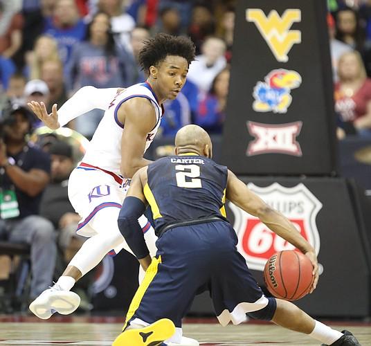 Kansas guard Devonte' Graham (4) defends against West Virginia guard Jevon Carter (2) during the second half, Saturday, March 10, 2018 at Sprint Center in Kansas City, Mo.