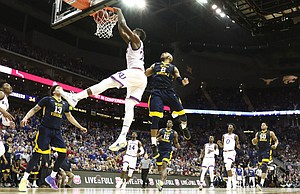 Kansas forward Silvio De Sousa (22) dunks off of a lob jame during the first half, Saturday, March 10, 2018 at Sprint Center in Kansas City, Mo.