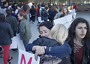 Lawrence High School seniors Grayson Rodriquez, center left, and Mariah Kaufman, center right, hug at the conclusion of a student walkout protesting gun violence, Wednesday, March 14, 2018, at LHS.