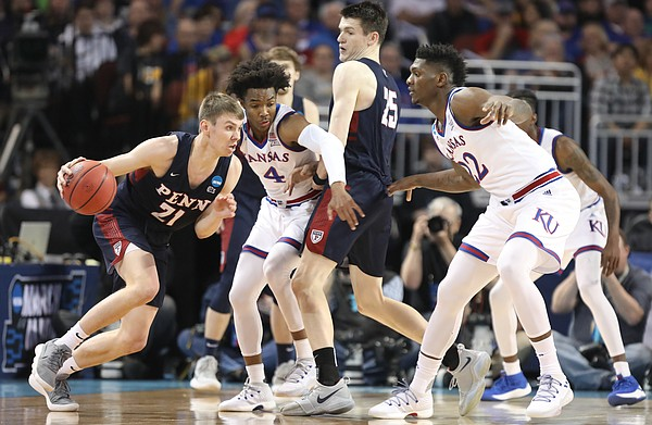 Kansas guard Devonte' Graham (4) fights his way around a pick set by Penn forward AJ Brodeur (25) as he defends Penn guard Ryan Betley (21) during the first half, Thursday, March 15, 2018 at Intrust Bank Arena in Wichita, Kan. At right is Kansas forward Silvio De Sousa (22).