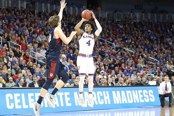 Kansas guard Devonte' Graham (4) puts a three over Penn guard Caleb Wood (10) during the second half, Thursday, March 15, 2018 at Intrust Bank Arena in Wichita, Kan.