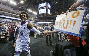 Kansas guard Devonte' Graham (4) slaps hands with fans as he leaves the court following the Jayhawks' first-round win over Penn, Thursday, March 15, 2018 at Intrust Bank Arena in Wichita, Kan.