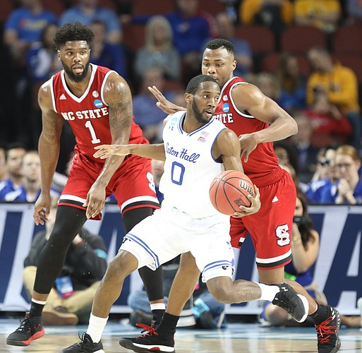 Seton Hall guard Khadeen Carrington (0) spins around North Carolina State guard Torin Dorn (2) during the second half, Thursday, March 15, 2018 at Intrust Bank Arena in Wichita, Kan. At left is North Carolina State forward Lennard Freeman (1).