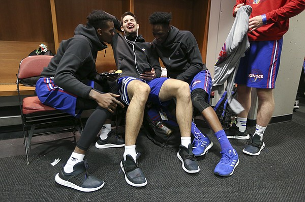 Kansas guards Lagerald Vick, left, Sam Cunliffe and Marcus Garrett laugh over a video on Twitter while in the team locker room on Friday, March 16, 2018 at Intrust Bank Arena in Wichita, Kan.