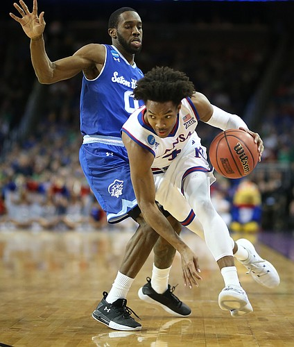 Kansas guard Devonte' Graham (4) drives against Seton Hall guard Khadeen Carrington (0) during the first half, Saturday, March 17, 2018 in Wichita, Kan.