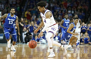 Kansas guard Devonte' Graham (4) comes away with a ball that was nearly stolen late in the second half, Saturday, March 17, 2018 in Wichita, Kan.
