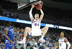 Kansas forward Mitch Lightfoot (44) delivers on a lob jam from Kansas guard Devonte' Graham (4) before Seton Hall guard Myles Powell (13) late in the second half, Saturday, March 17, 2018 in Wichita, Kan.