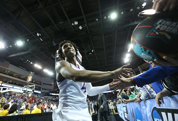 Kansas guard Devonte' Graham slaps hands with fans as he leaves the court following the Jayhawks' win, Saturday, March 17, 2018 in Wichita, Kan.