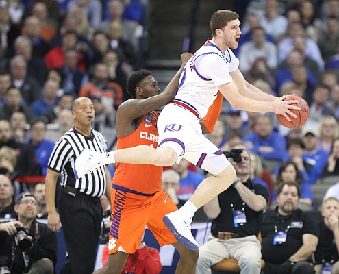 Kansas guard Sviatoslav Mykhailiuk (10) is fouled by Clemson forward Elijah Thomas (14) on the rebound during the first half, Friday, March 23, 2018 at CenturyLink Center in Omaha, Neb.